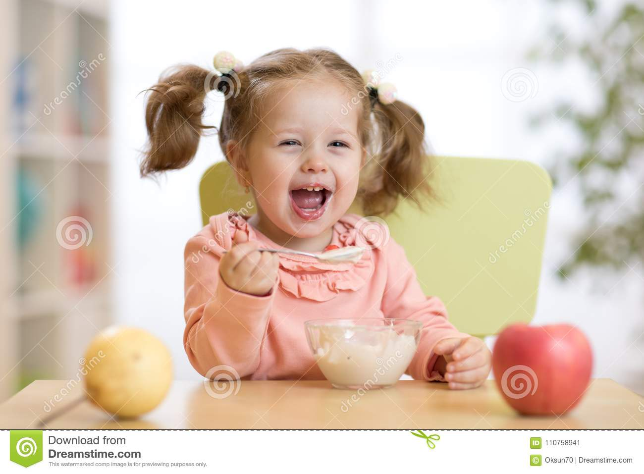 Cheerful baby child eating food itself with a spoon
