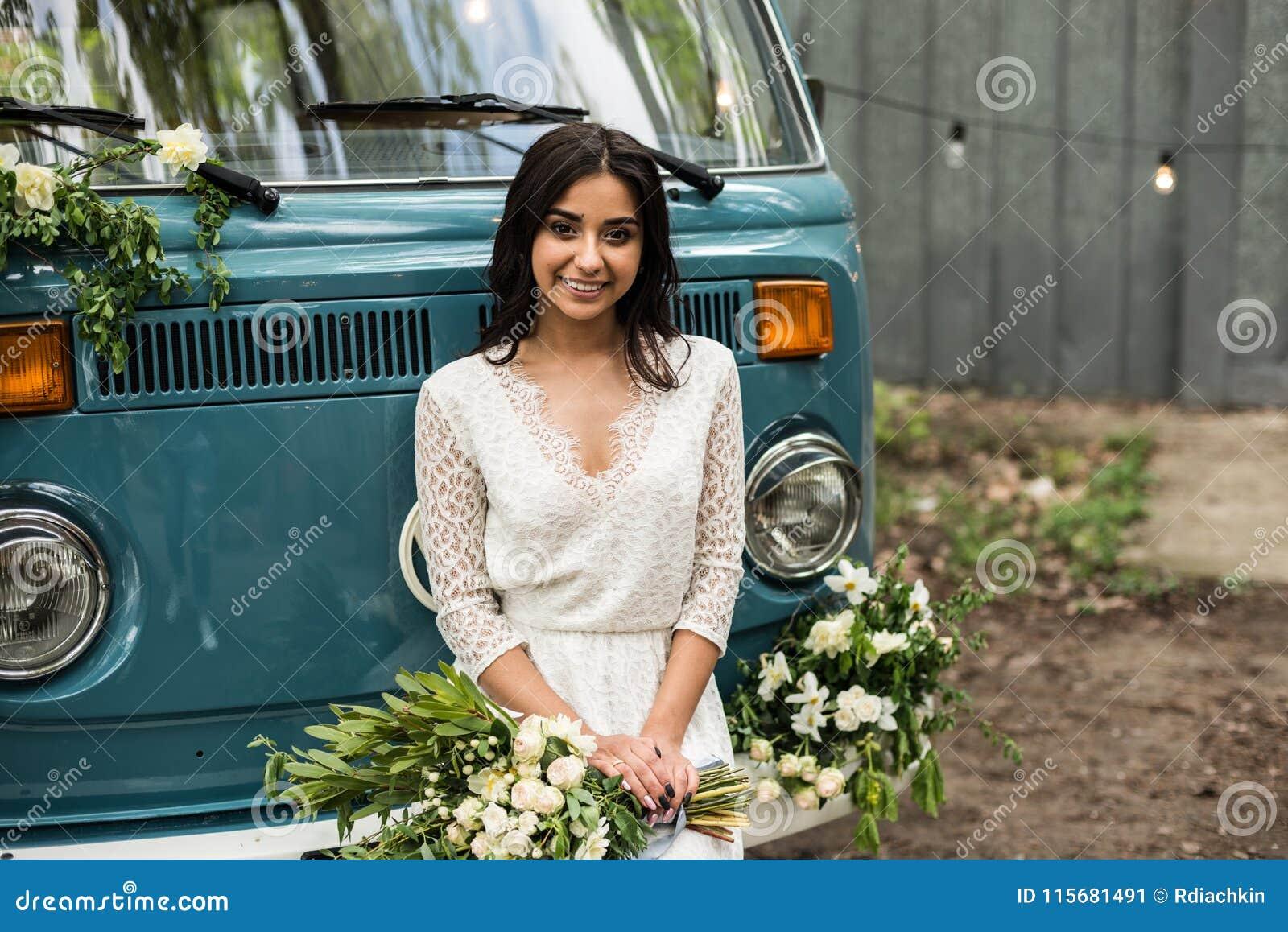 Cheerful happy young bride sit on the bumper retro-minibus. Close-up.