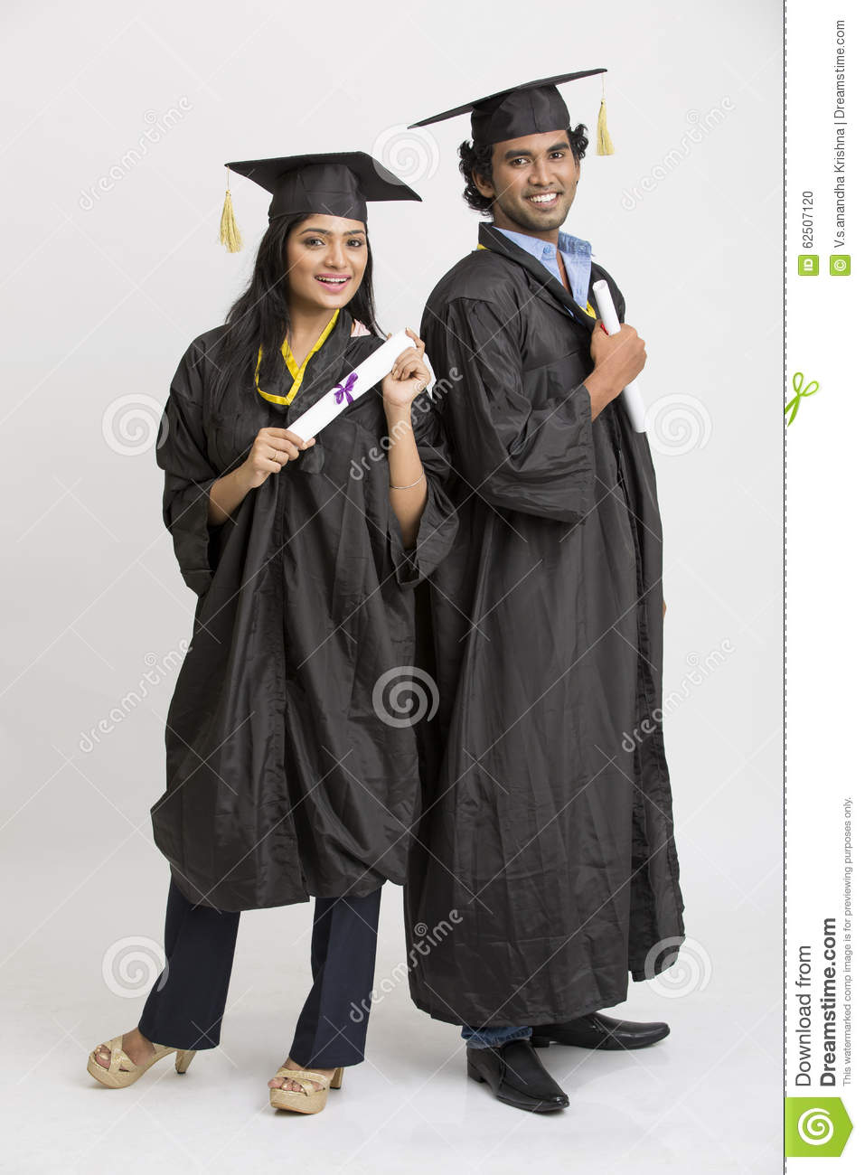 Cheerful Indian College Graduates Wearing Cap And Gown Holding ...