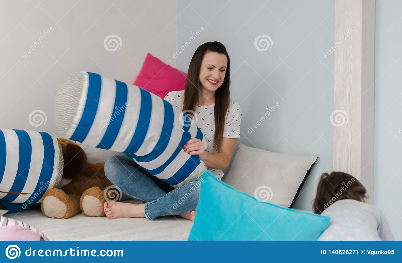 Cheerful kids and parents having pillow fight on bed at home