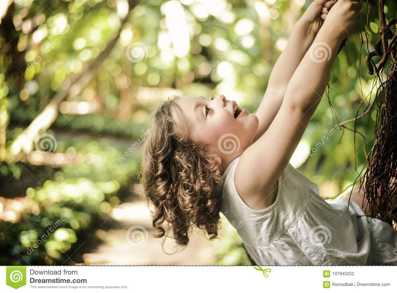 Cheerful, little girl climbing on a palm tree