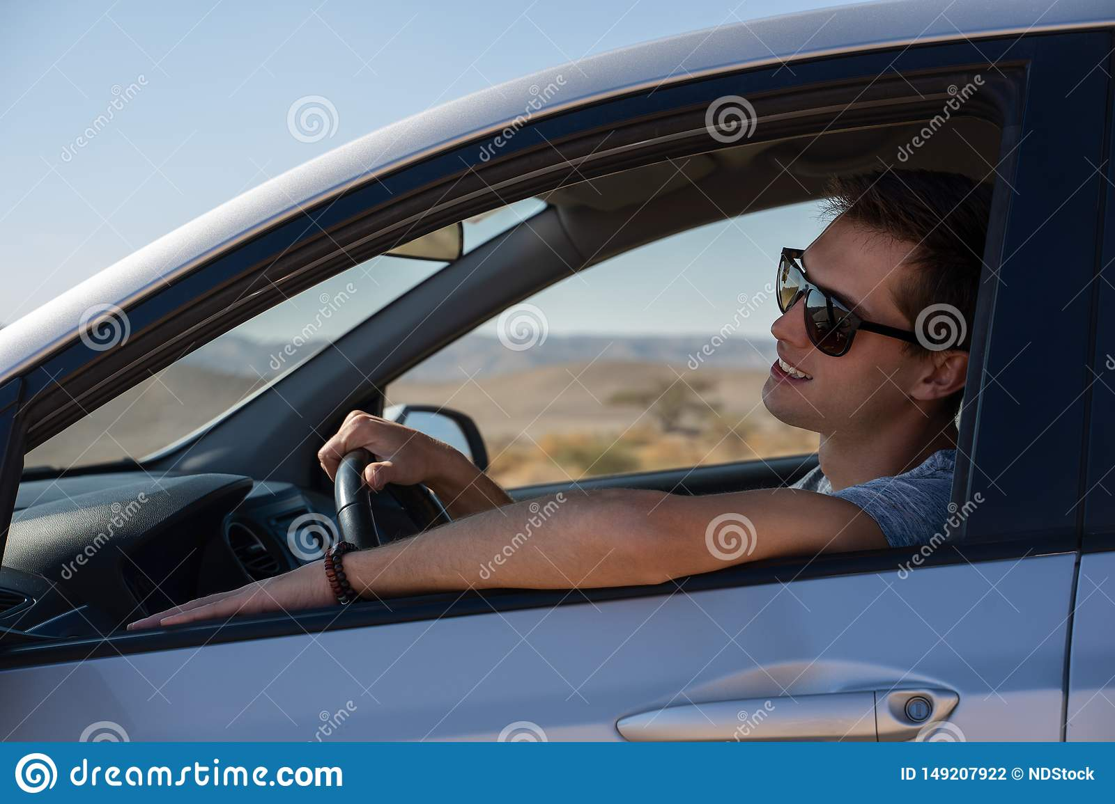 Happy young man driving a rented car in the desert of israel