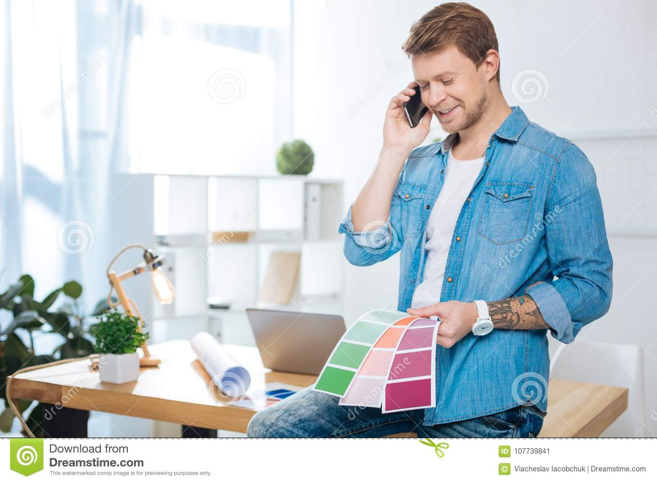 Cheerful man talking on the phone while holding color palettes