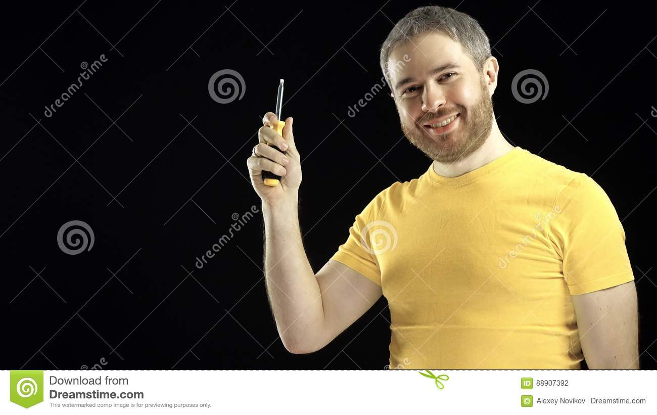 Cheerful man in yellow tshirt holds screwdriver. DIY, repair, amateur  construction or home improvement concepts