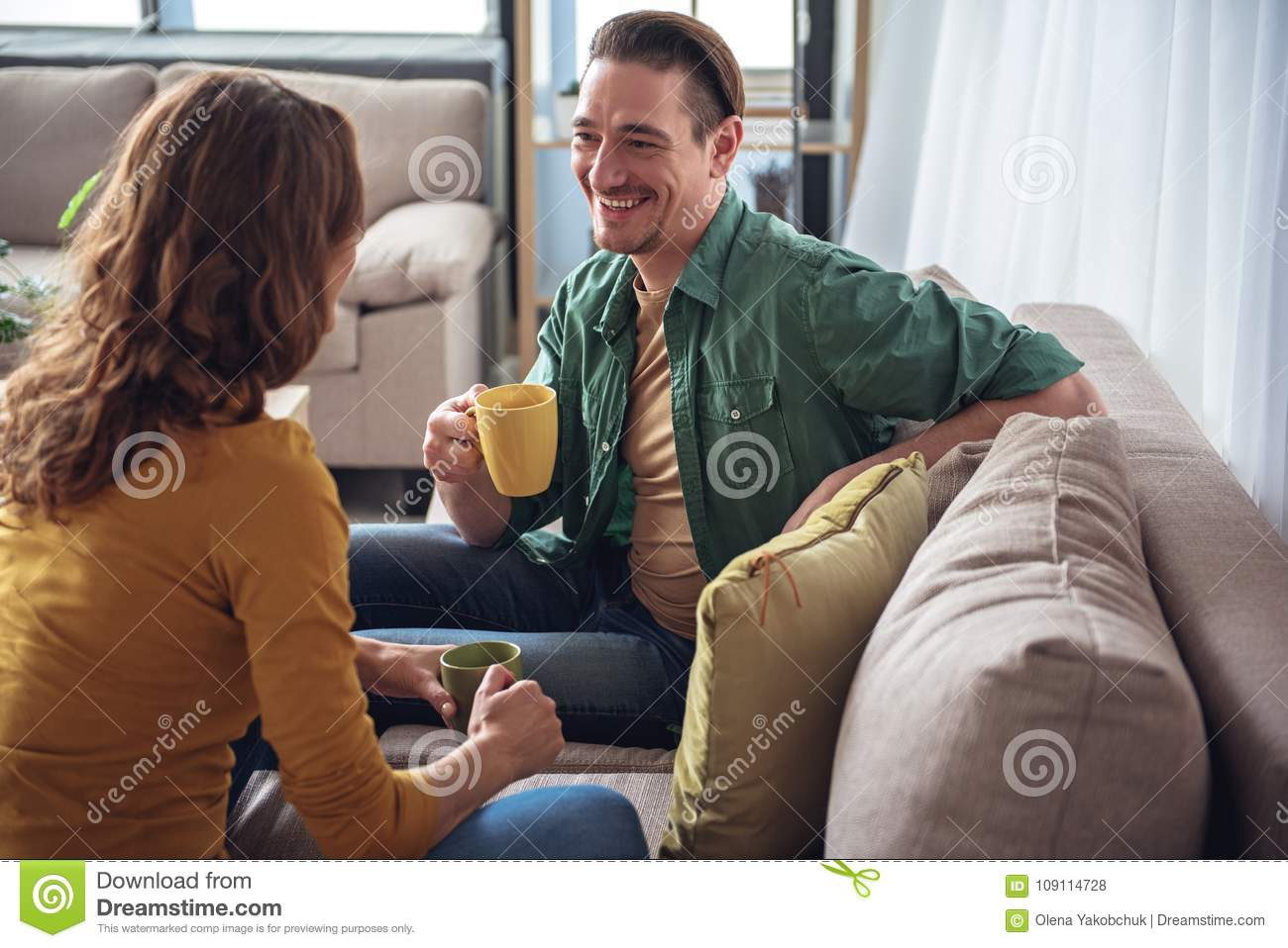 Cheerful married couple resting on sofa in living room together. They are  drinking tea and laughing. Pleasant conversation concept