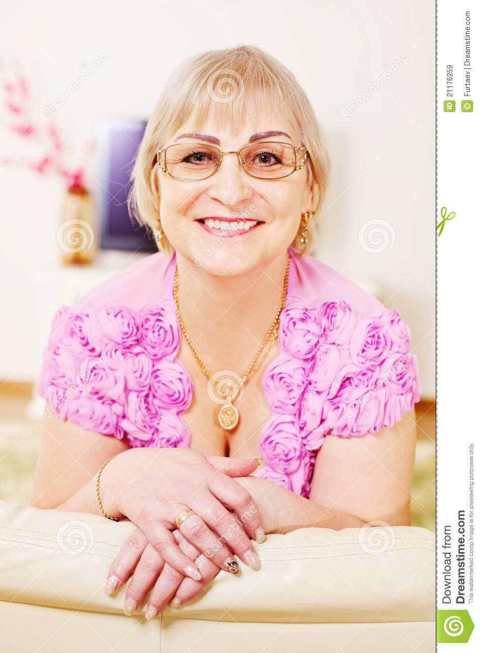 Cheerful mature woman on sofa