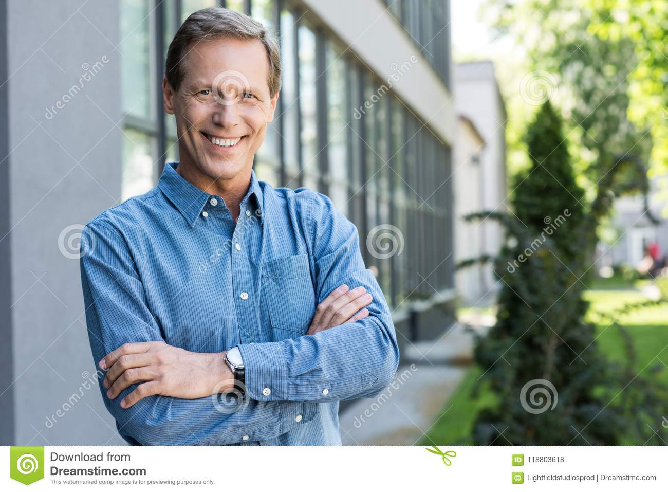 cheerful middle aged businessman posing with crossed arms near office