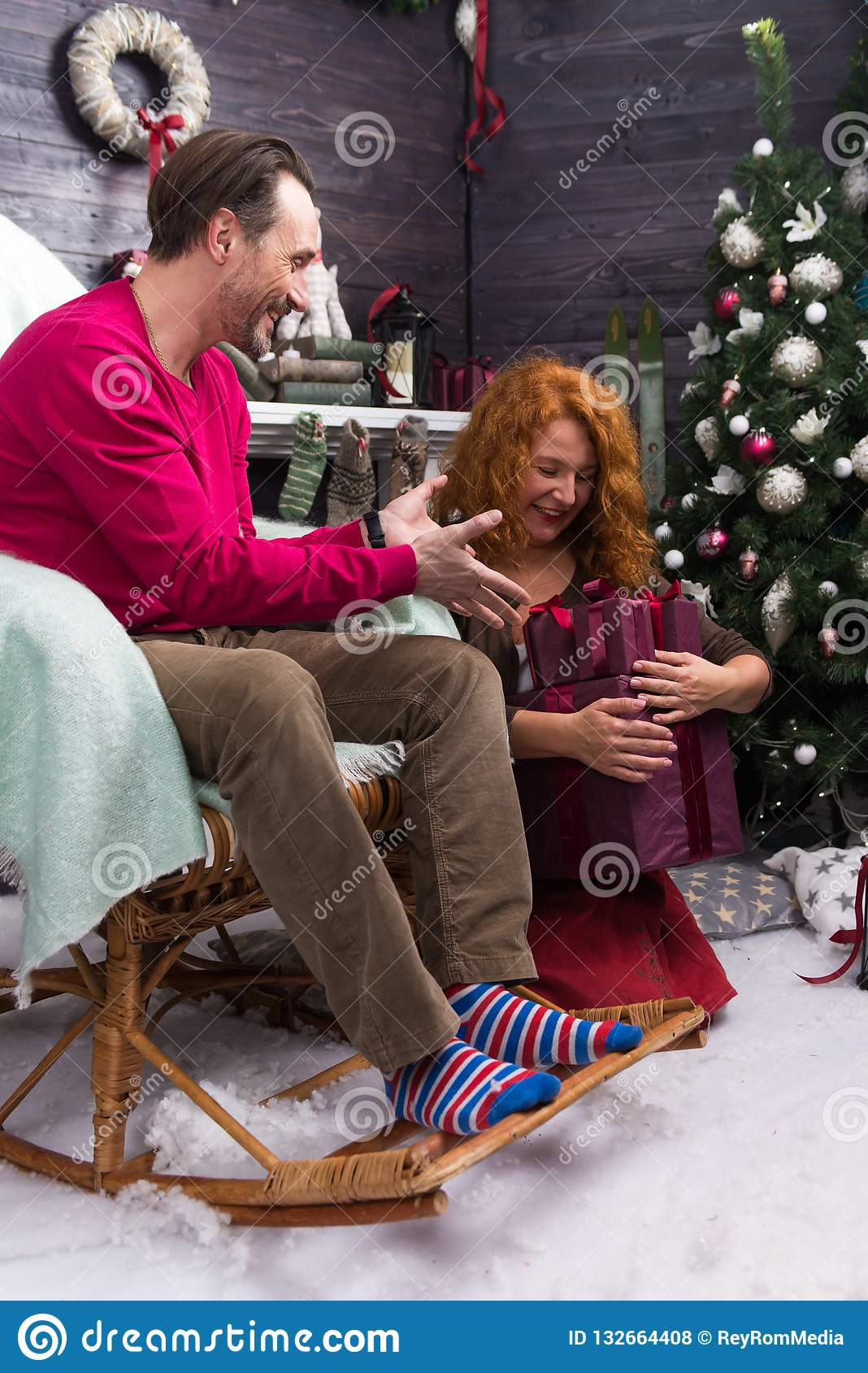 Excited man smiling and looking at the presents in womans hands