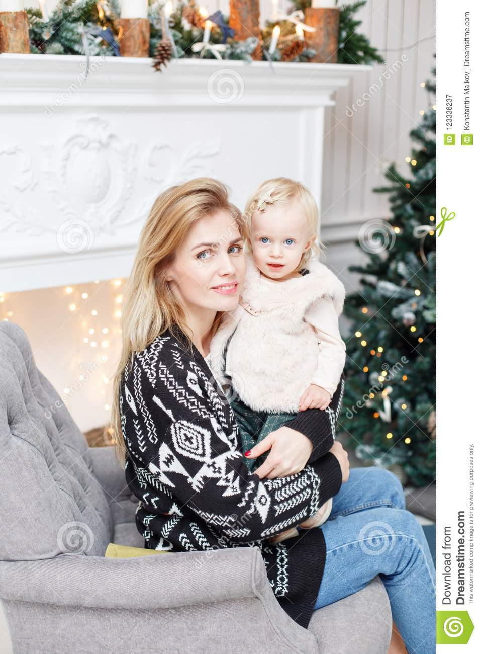 Cheerful mom embraces her cute baby daughter . Parent and little child having fun near Christmas tree indoors. Loving