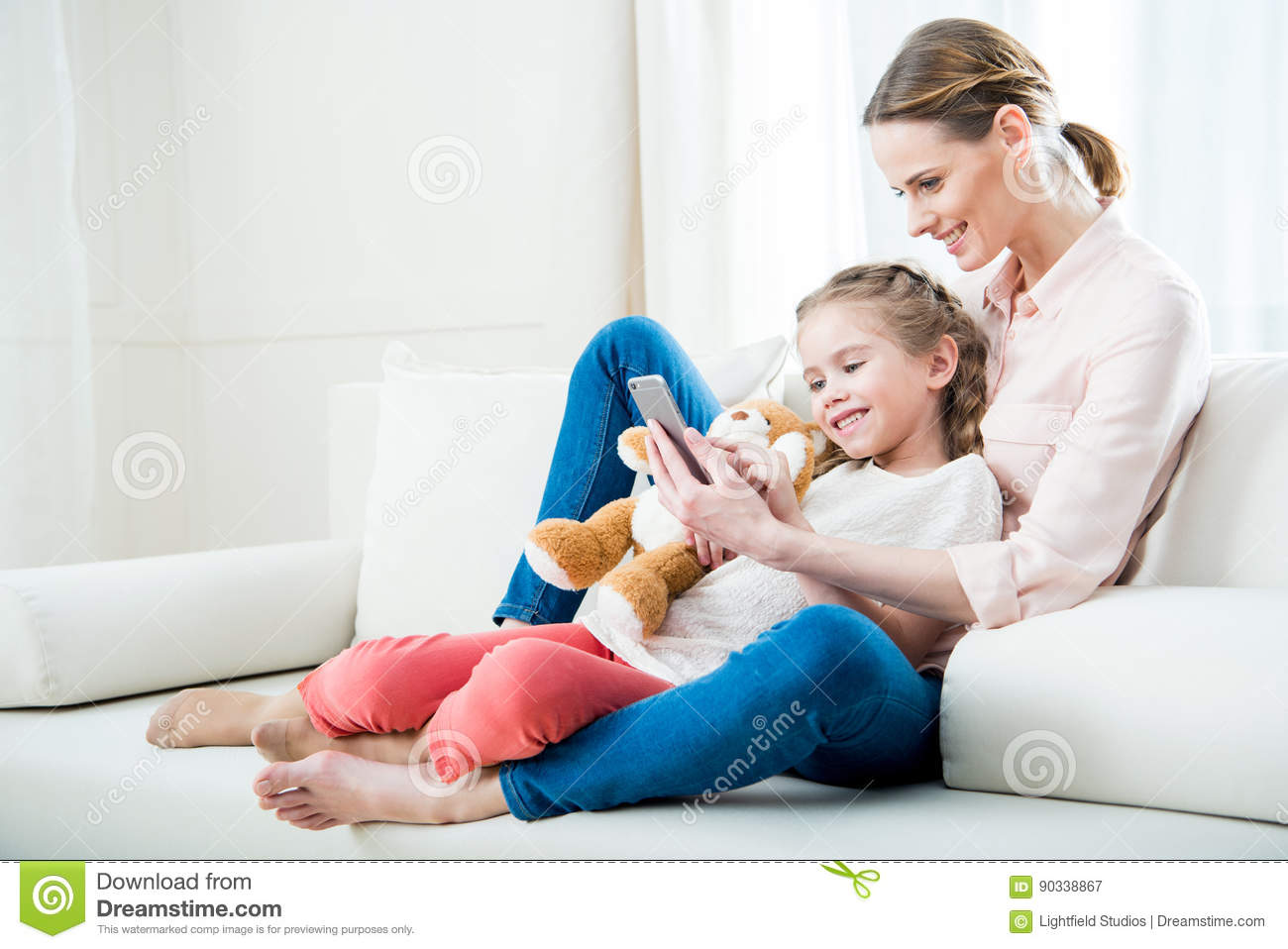 Cheerful mother and daughter using smartphone together