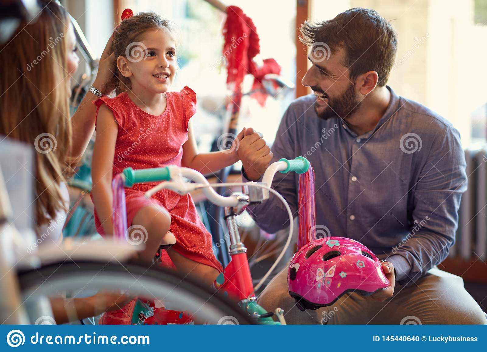Cheerful mother and father buying new bicycle for little girl in bike shop