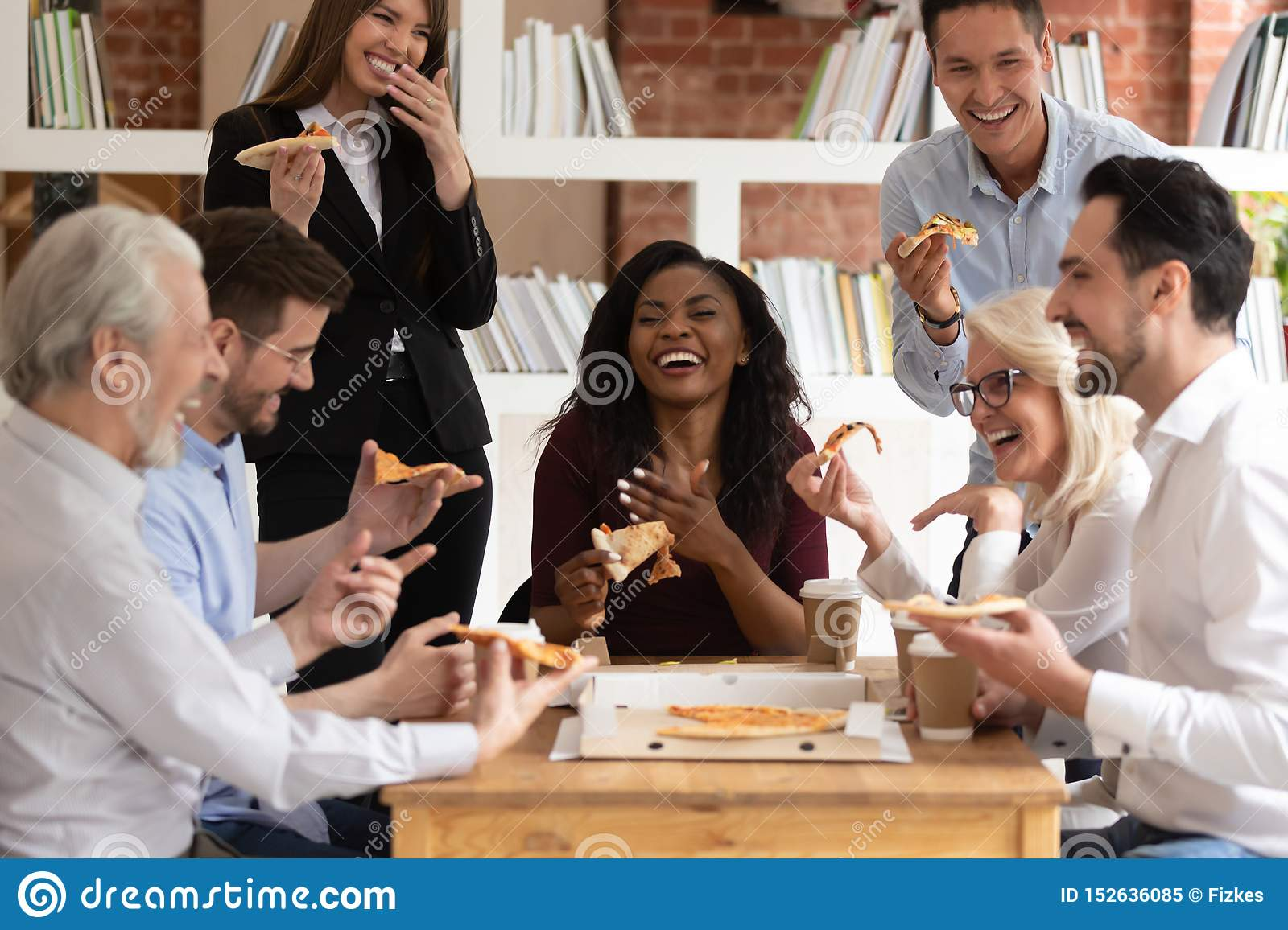 cheerful-multiracial-office-business-people-laugh-share-takeaway-pizza-together-friendly-happy-diverse-young-old-employees-152636085.jpg