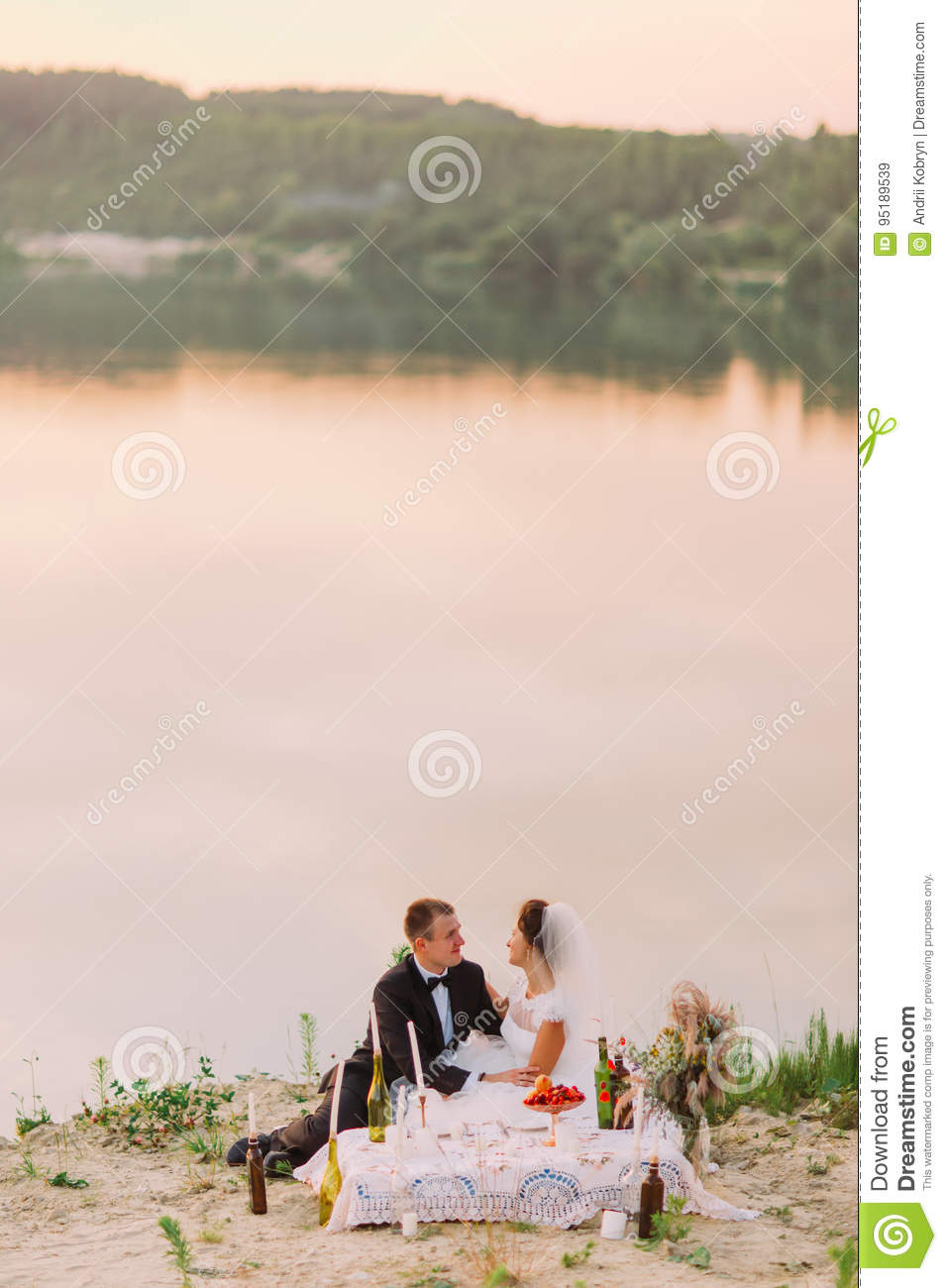 The cheerful newlywed couple is enjoying the wedding picnic at the background of the magnificent river.