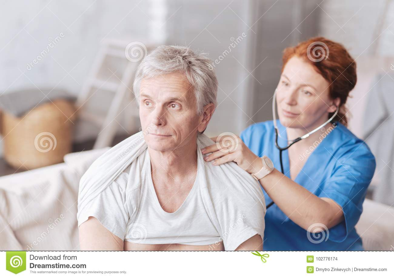 Cheerful nurse with stethoscope listening to lung sounds of patient