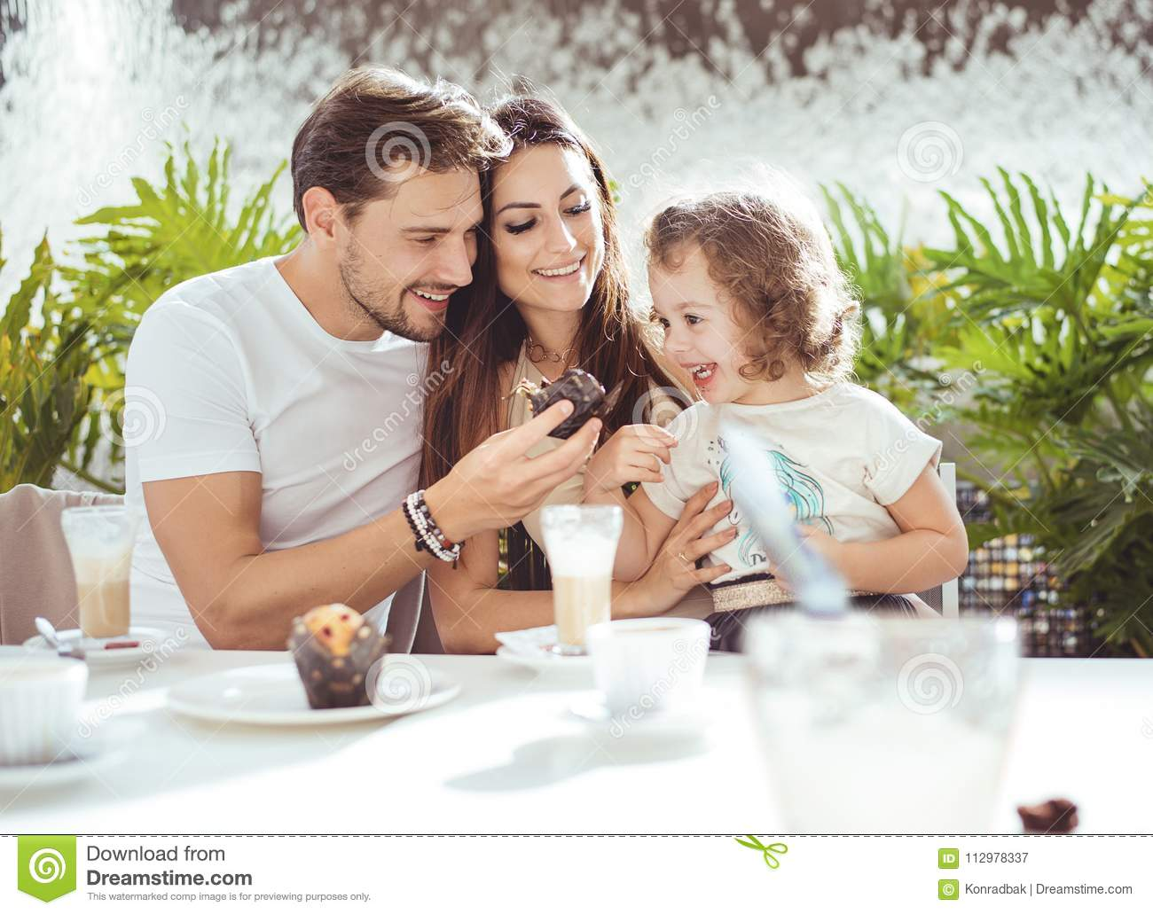 Cheerful parents feeding their daughter