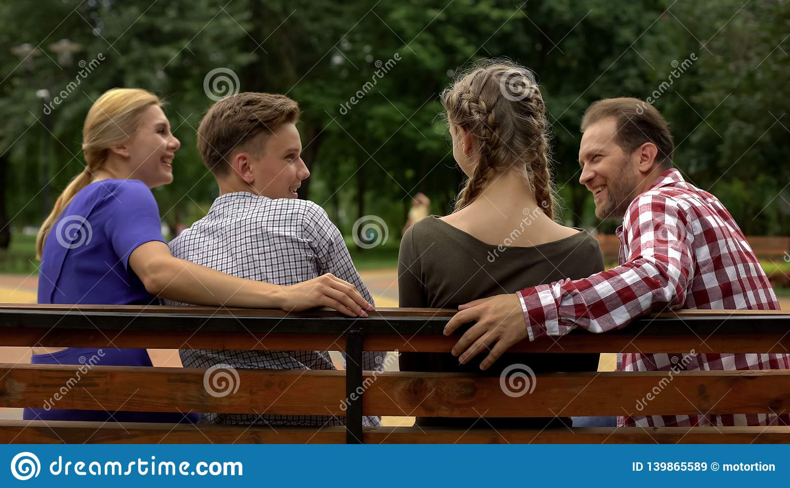 Cheerful parents and their teenage children planning weekend on bench in park
