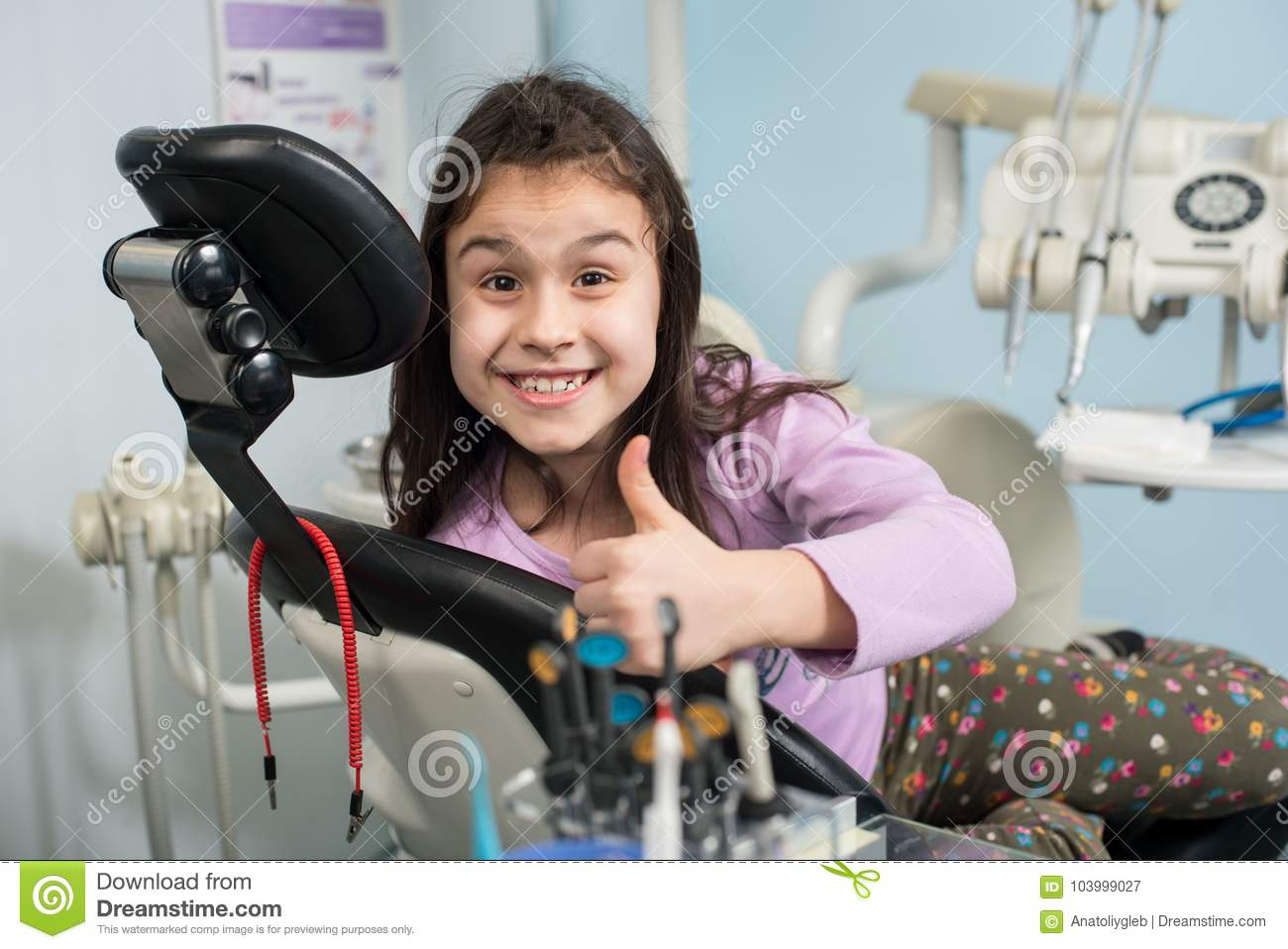 Cheerful patient girl showing thumbs up at dental clinic office. Medicine, stomatology and health care concept