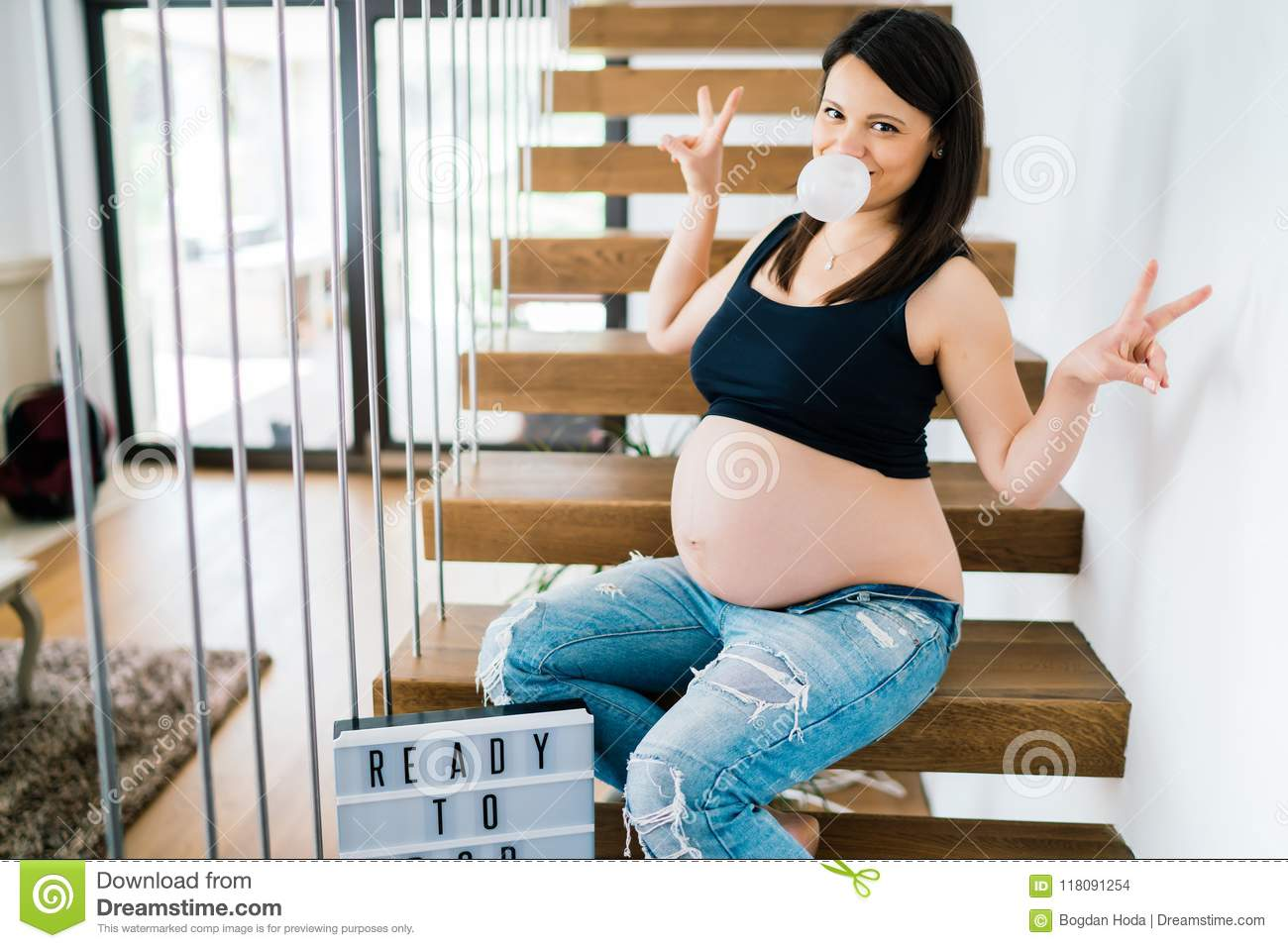 Cheerful portrait of young pregnant woman sitting on stairs enjoying life. modern lifestyle details - new home and baby coming