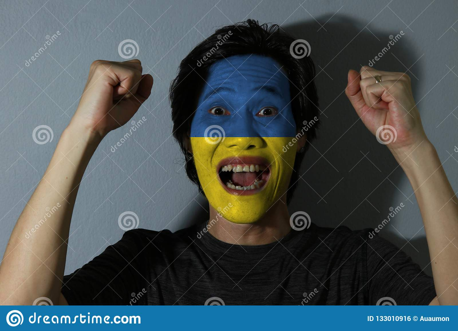 Cheerful portrait of a man with the flag of Ukraine painted on his face on grey background. The concept of sport or nationalism.