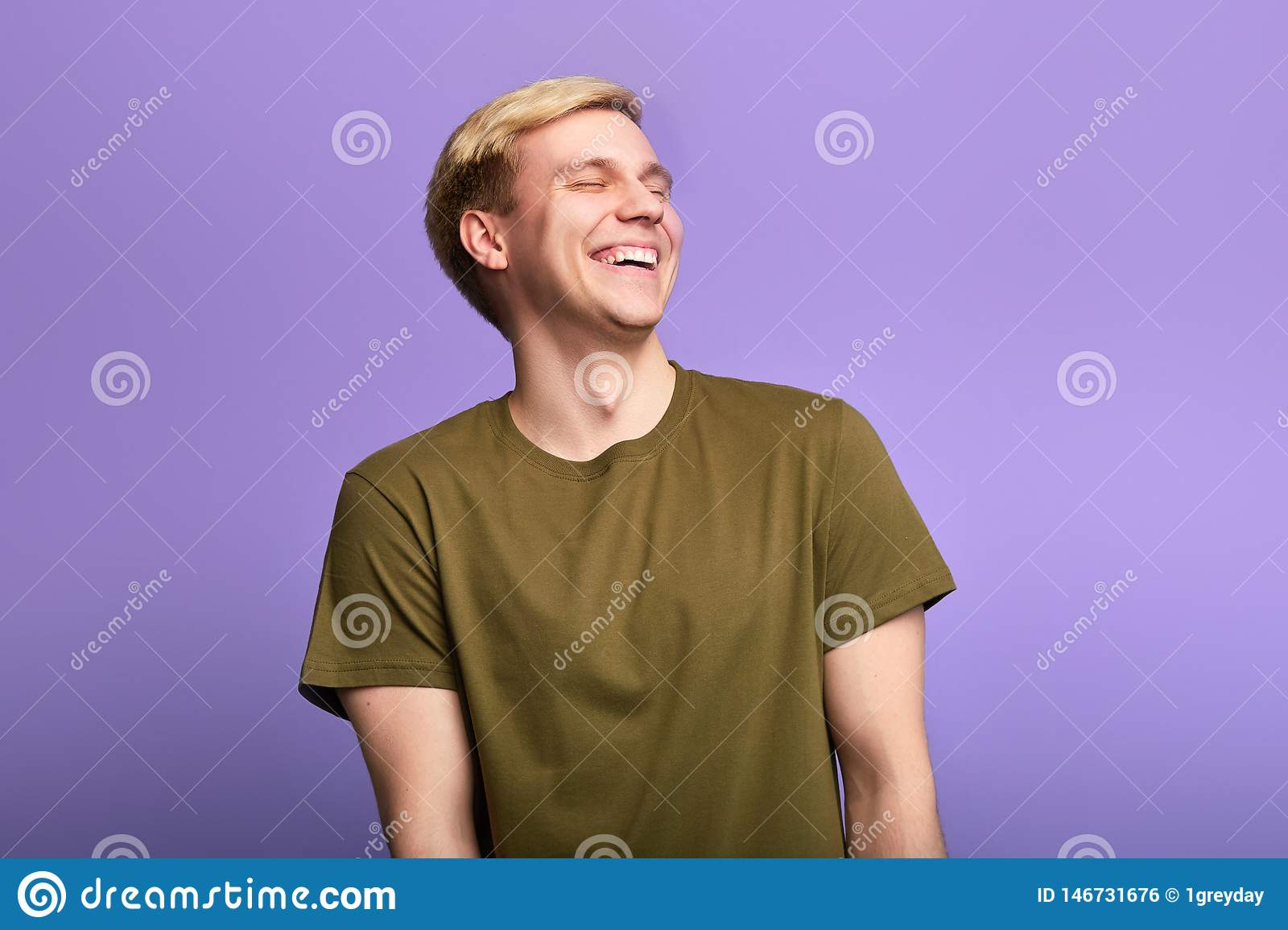 Cheerful positive man with closed eyes, laughs positively