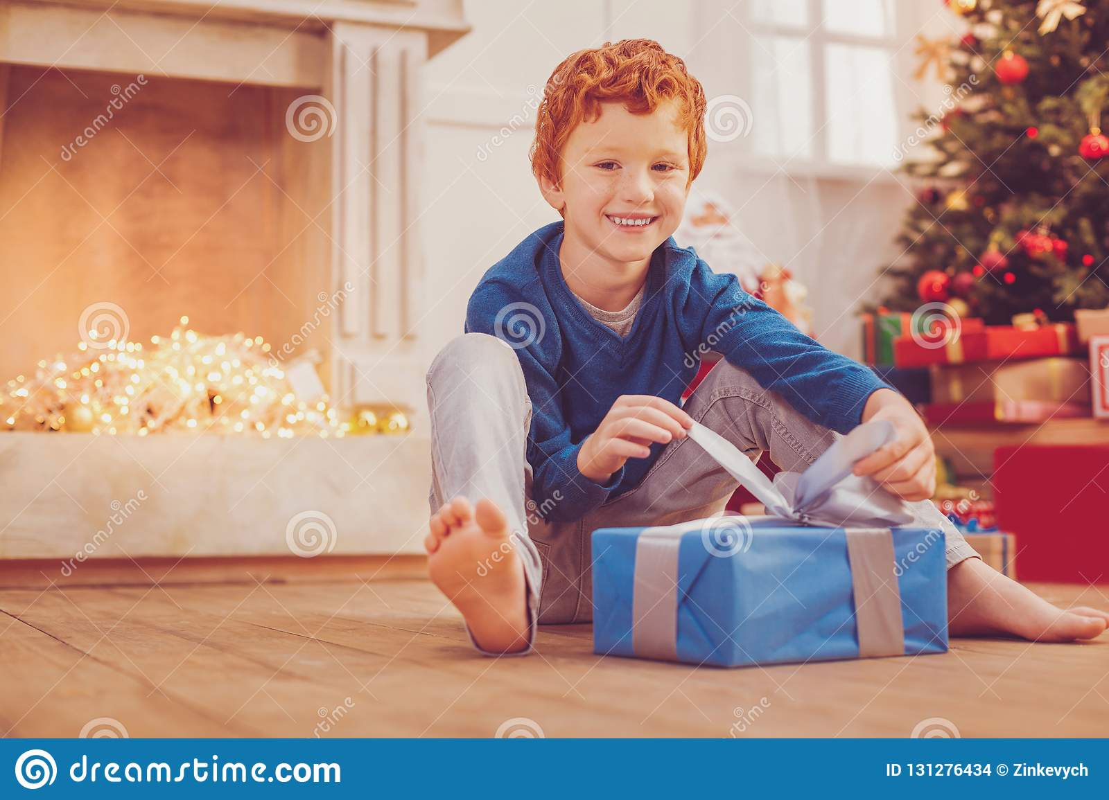 Cheerful preteen boy opening his Christmas present