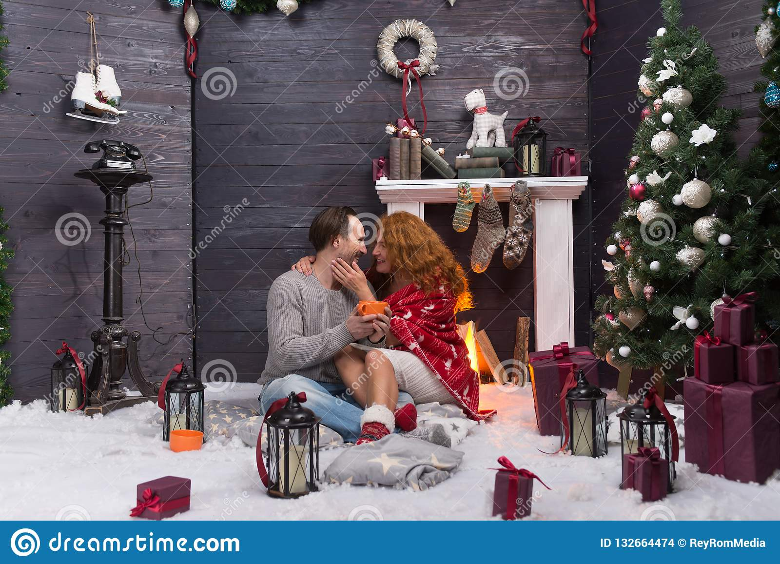 Happy woman in warm blanket sitting near fireplace and hugging her husband