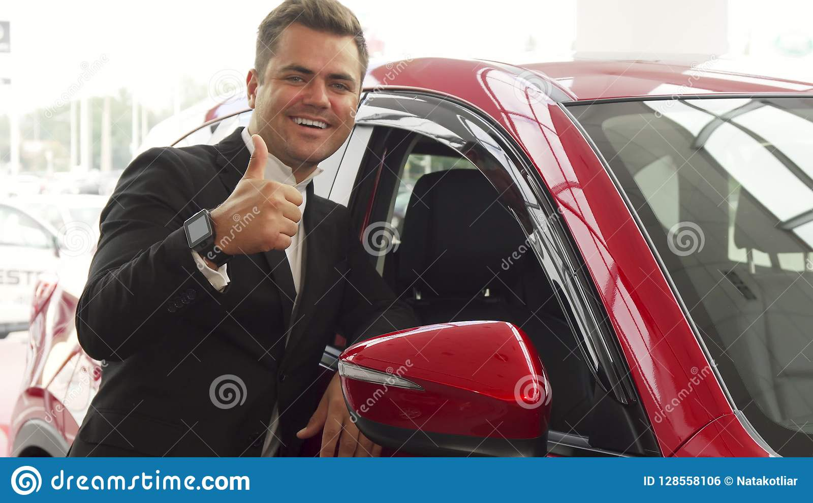 A cheerful salesman points to the excellent quality of the car