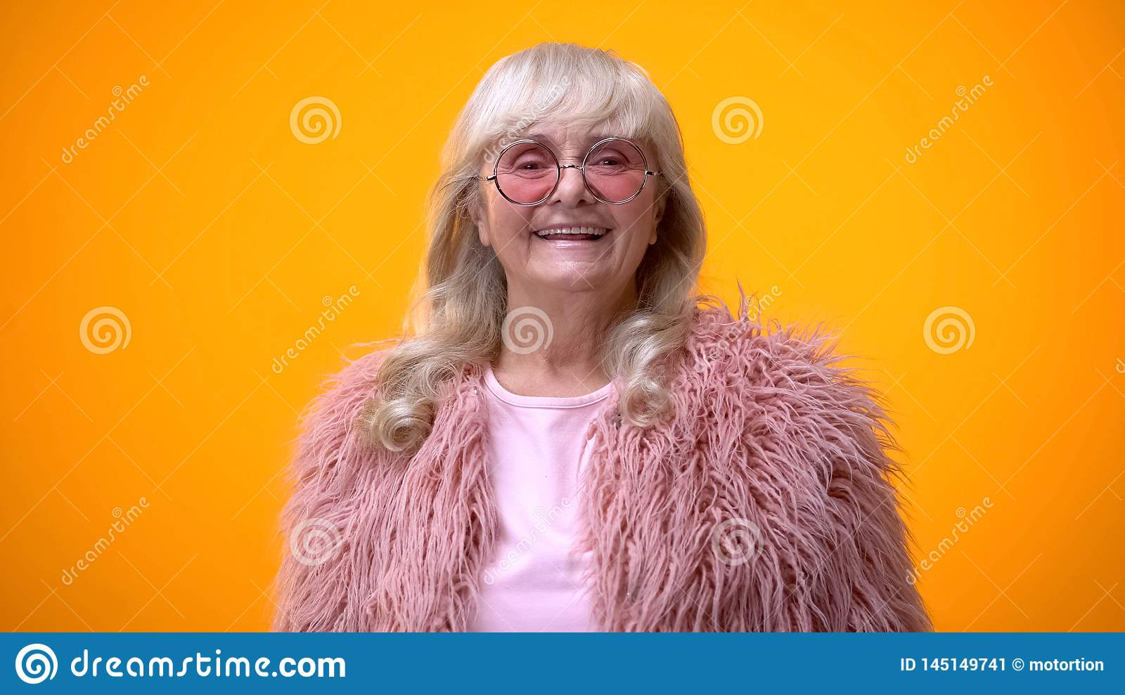 Cheerful senior woman in pink coat and round sunglasses smiling on camera