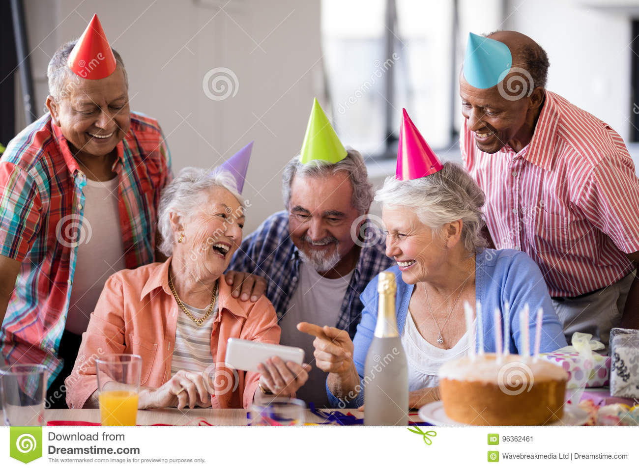 Cheerful senior woman showing mobile phone to friends in party