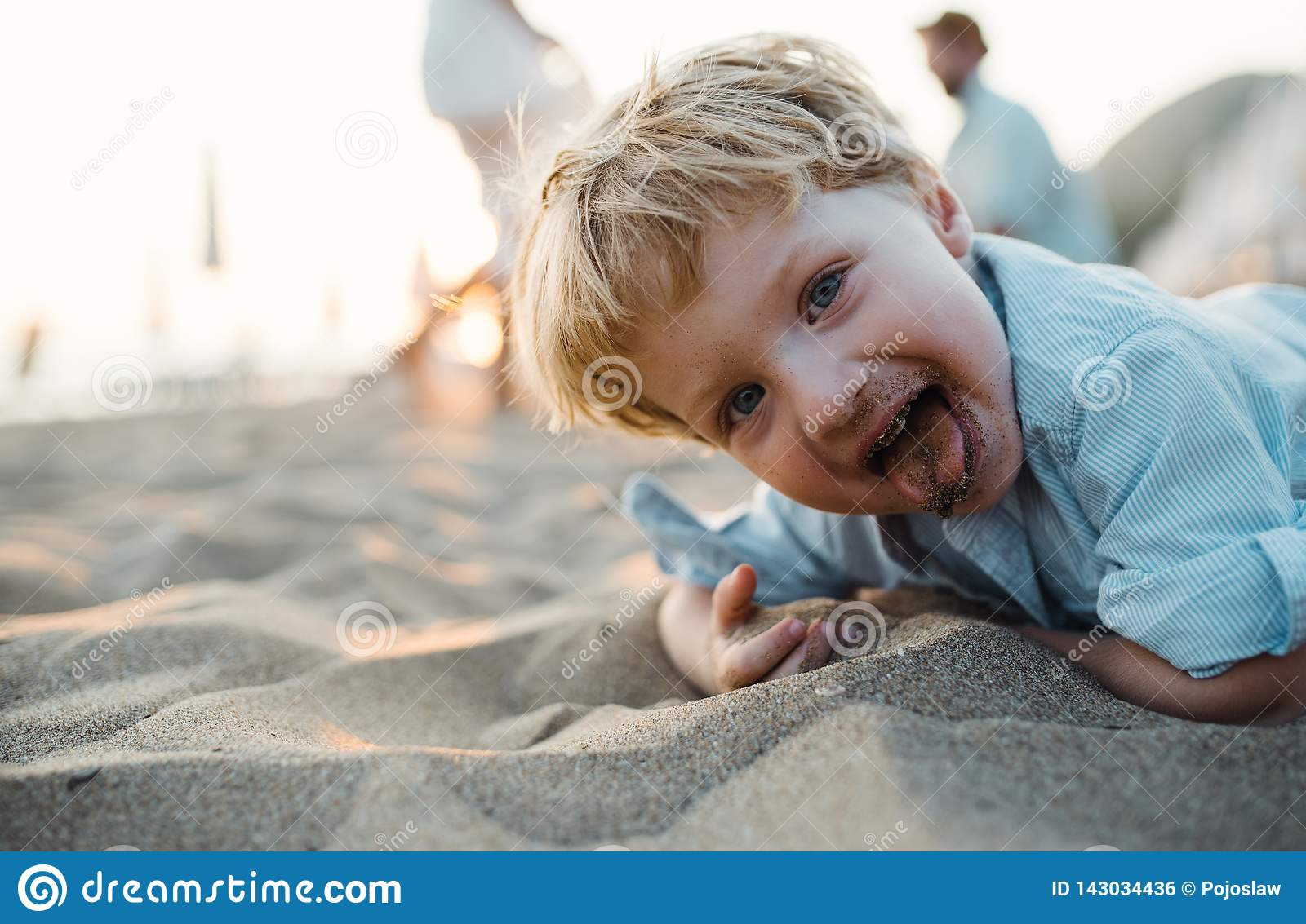A small toddler boy standing on beach on summer holiday, having fun.