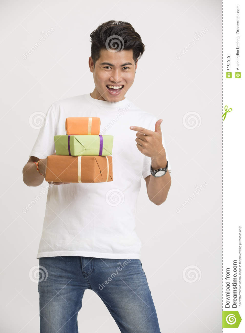 Cheerful smart Indian young man pointing with gift boxes