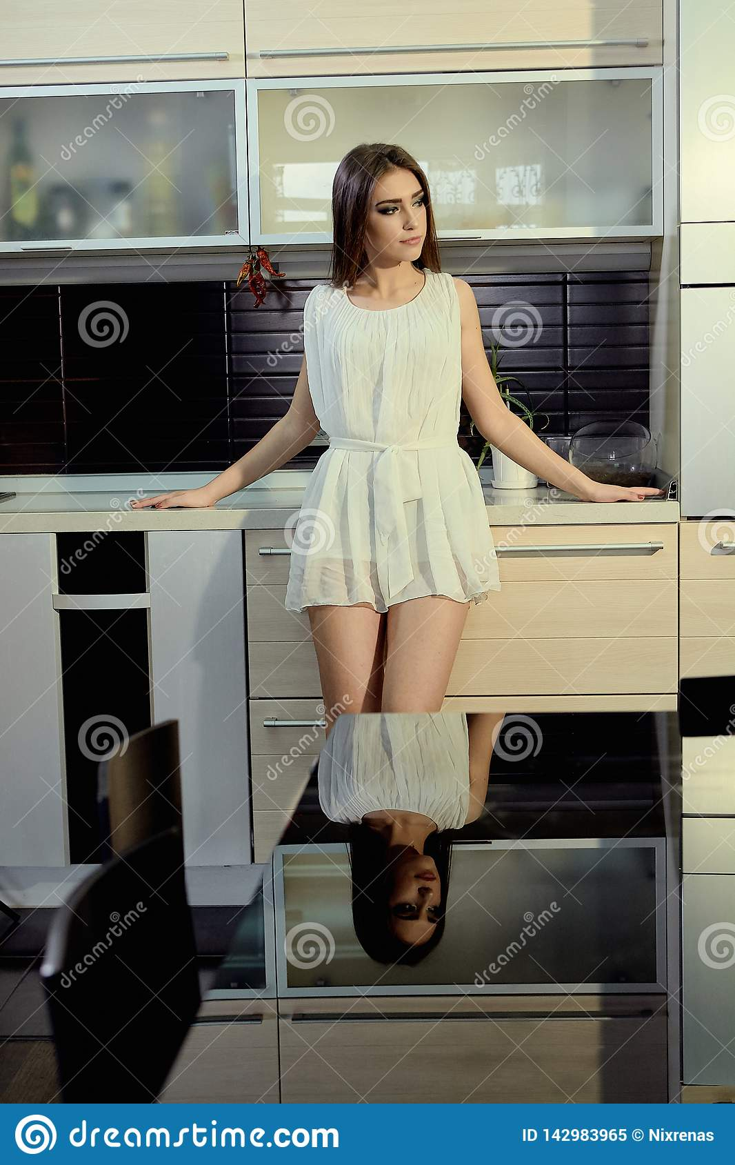 Cheerful smiling young white skin female with long brunette hair posing on the kitchen