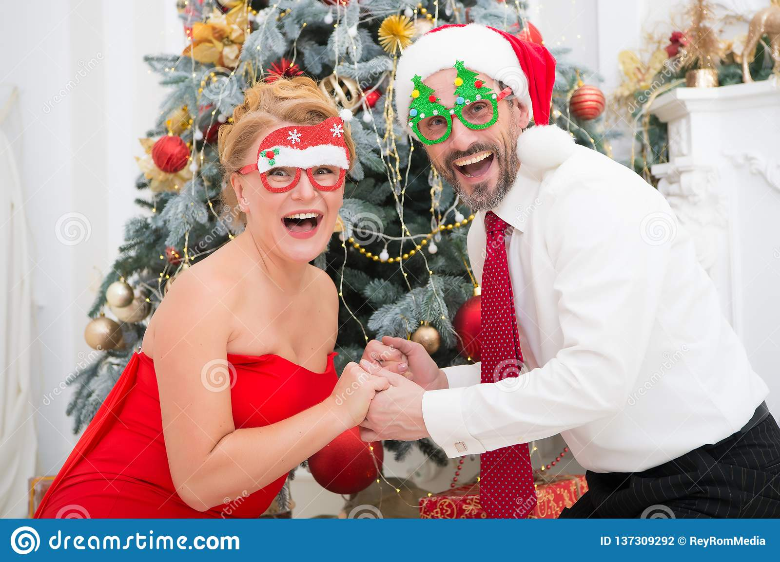 Cheerful stylish couple wearing party glasses and expressing surprise with Christmas tree on background