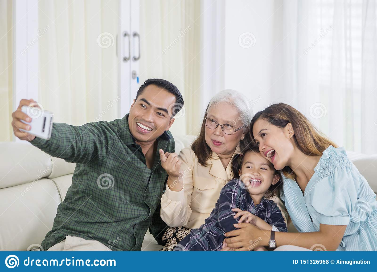 Cheerful three generation family takes selfie at home