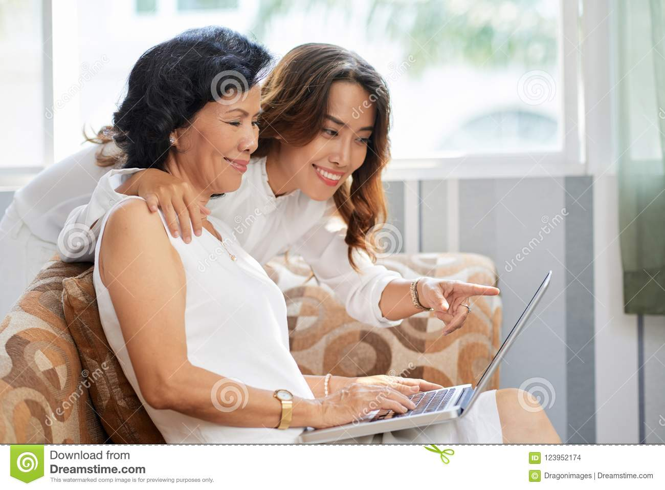 Cheerful Vietnamese Mother And Daughter Watching Videos Or Photos On Laptop Screen