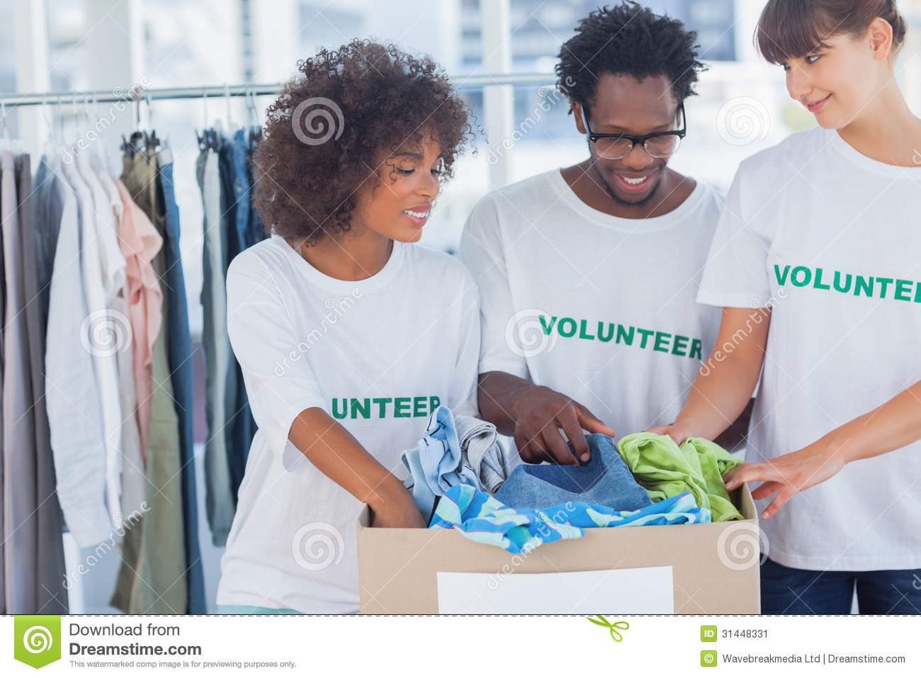 cheerful volunteers taking out clothes from a donation box