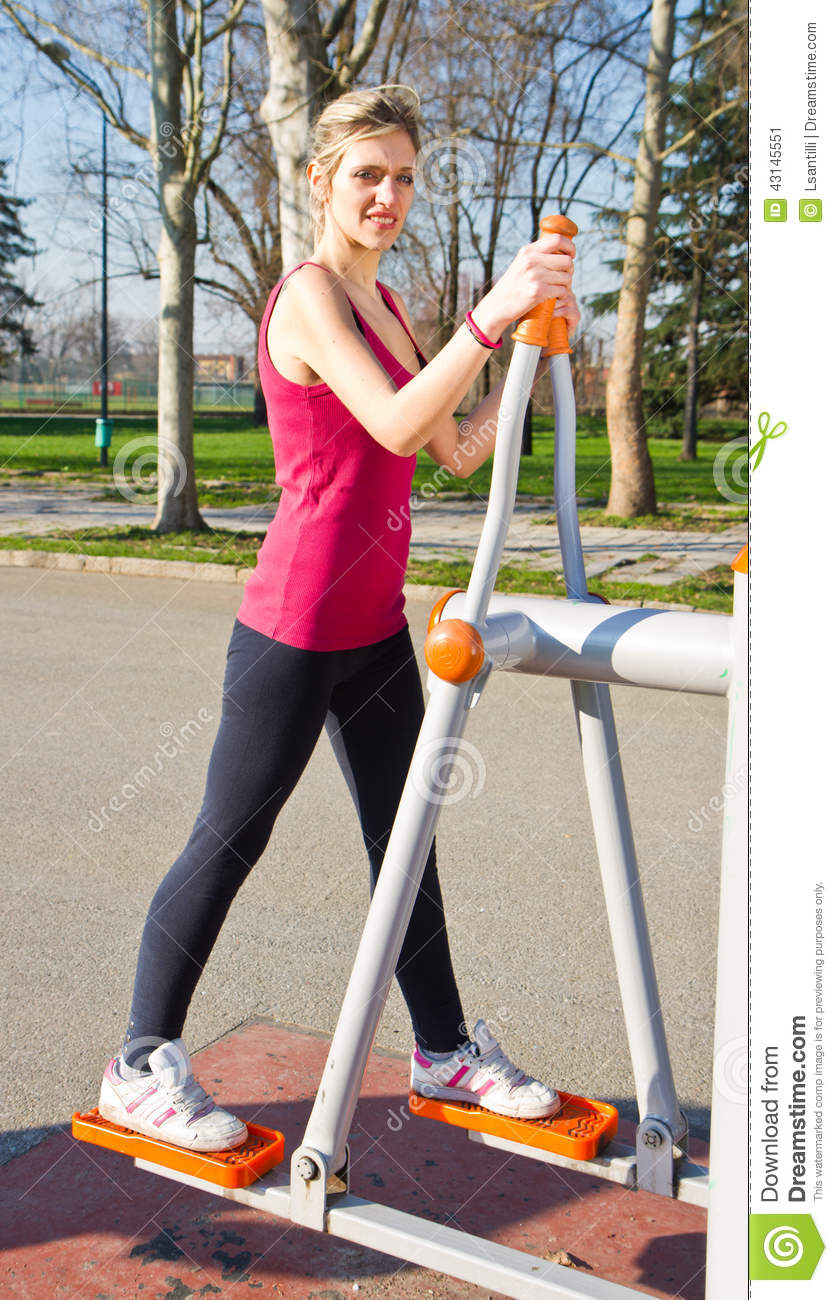 Cheerful woman in fitness wear exercising with equip