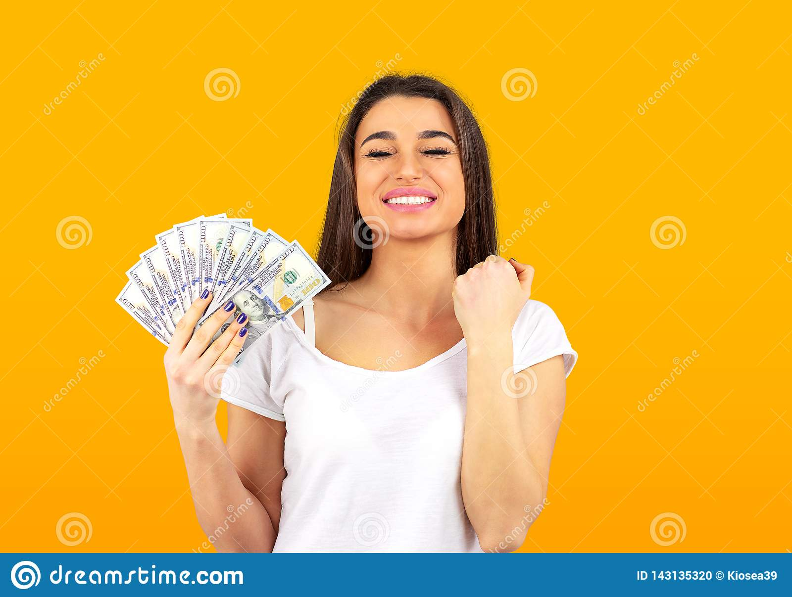 Cheerful woman holding money and celebrating success