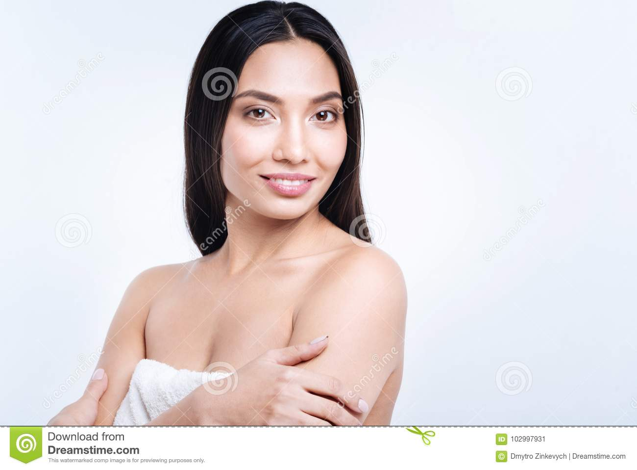 Cheerful woman with loose hair posing in towel