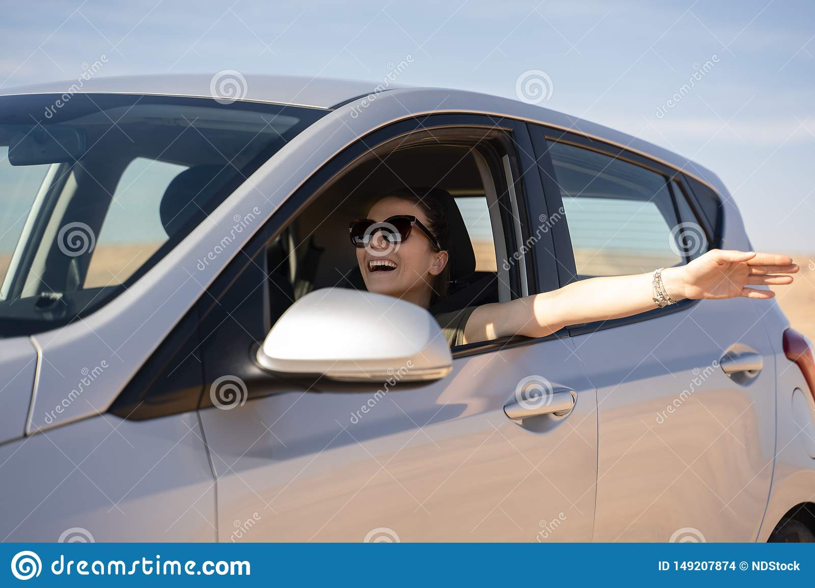 Happy young woman driving a rented car in the desert of israel