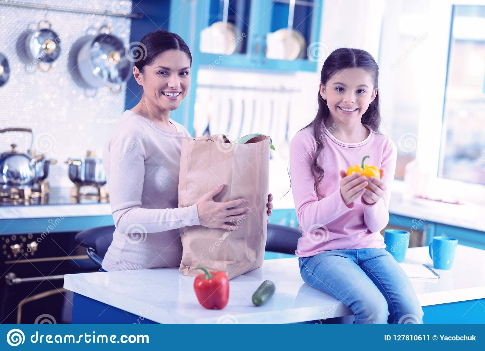 Cheerful woman standing with paper bag and her daughter sitting with yellow pepper