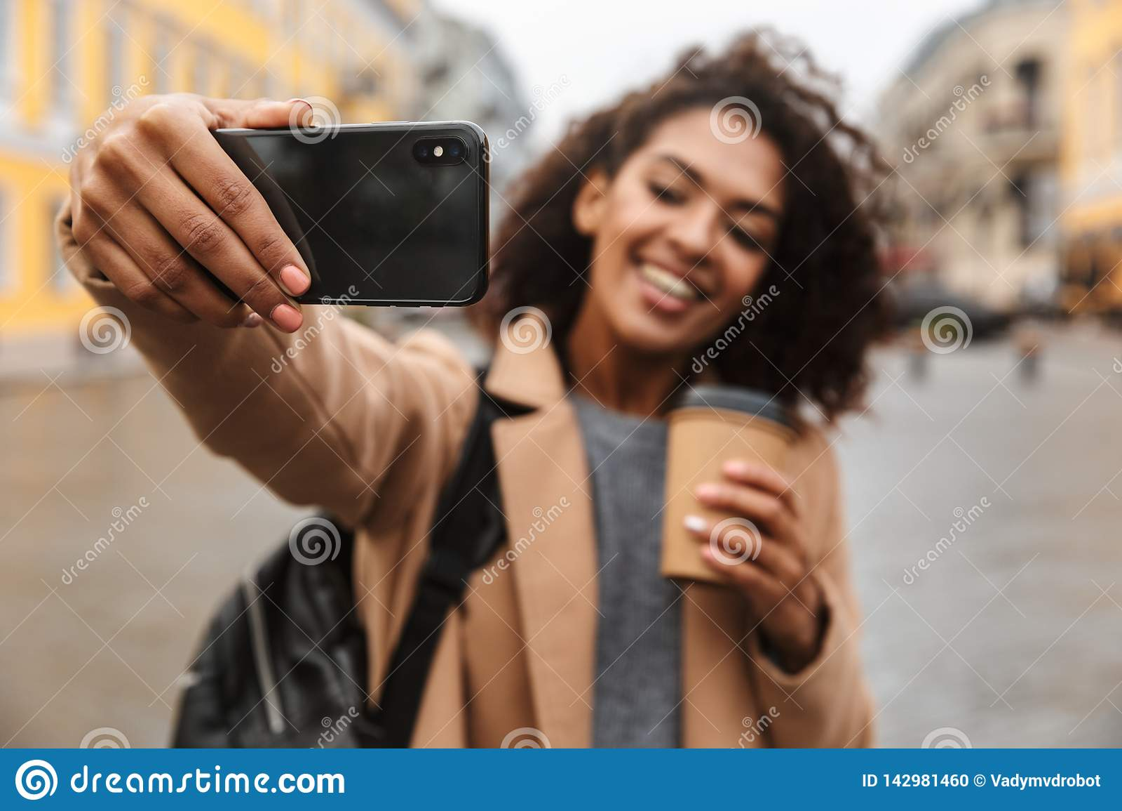 Cheerful young african woman wearing coat walking