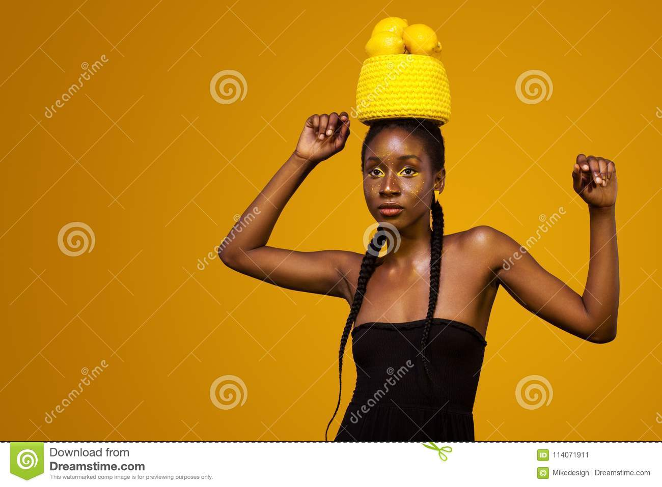 Cheerful young african woman with yellow makeup on her eyes. Female model against yellow background with yellow lemons.