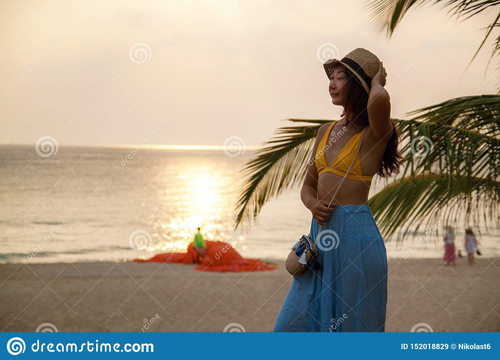 Cheerful young asian woman near palm tree on beach at sunset.