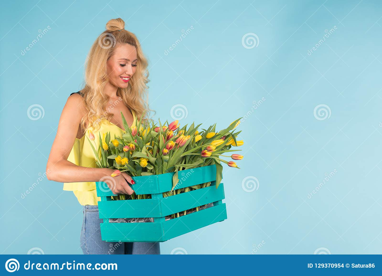 Cheerful young blonde woman florist with box of tulips over blue background with copy space