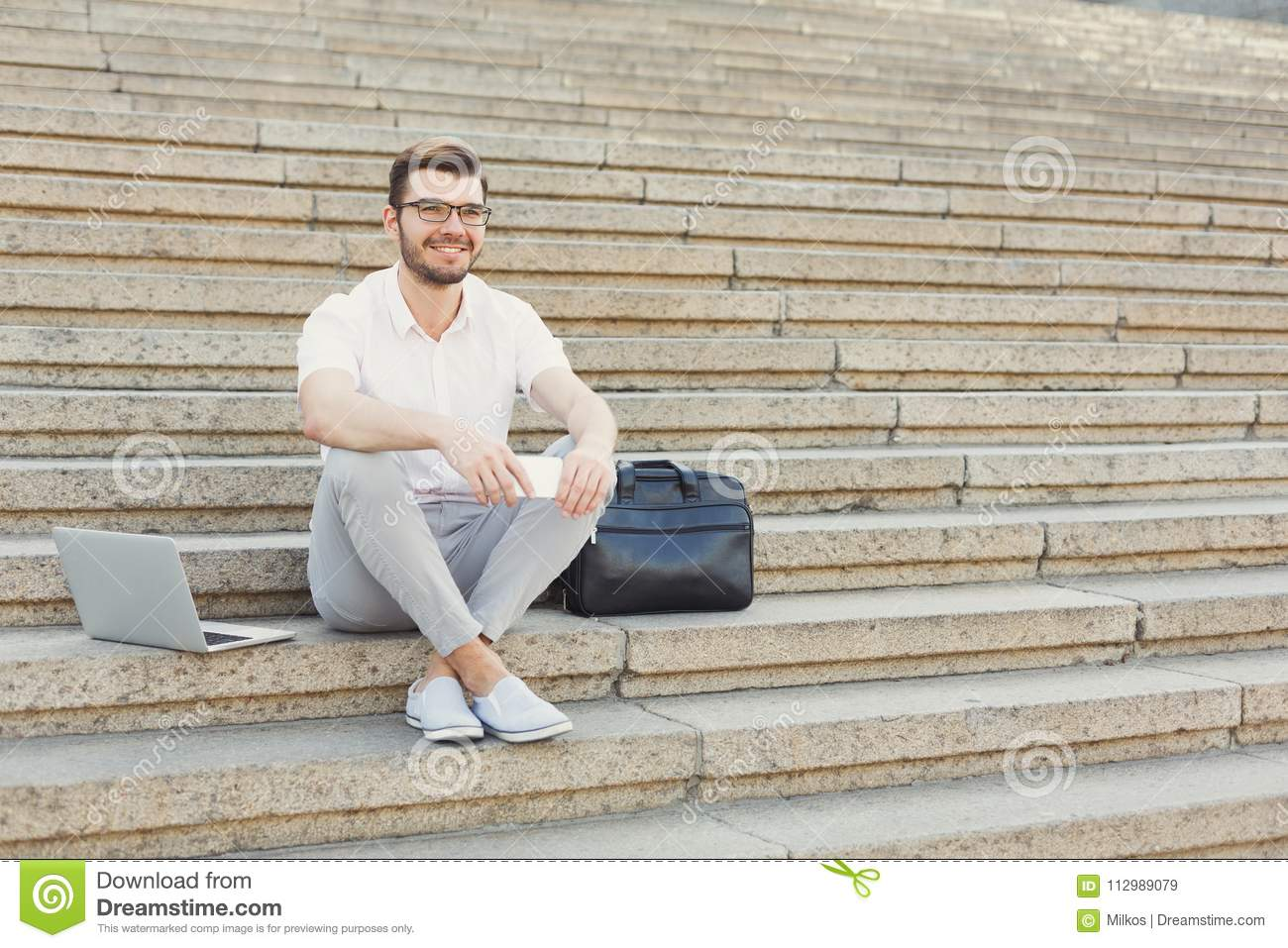 Cheerful young businessman using phone and laptop on stairs