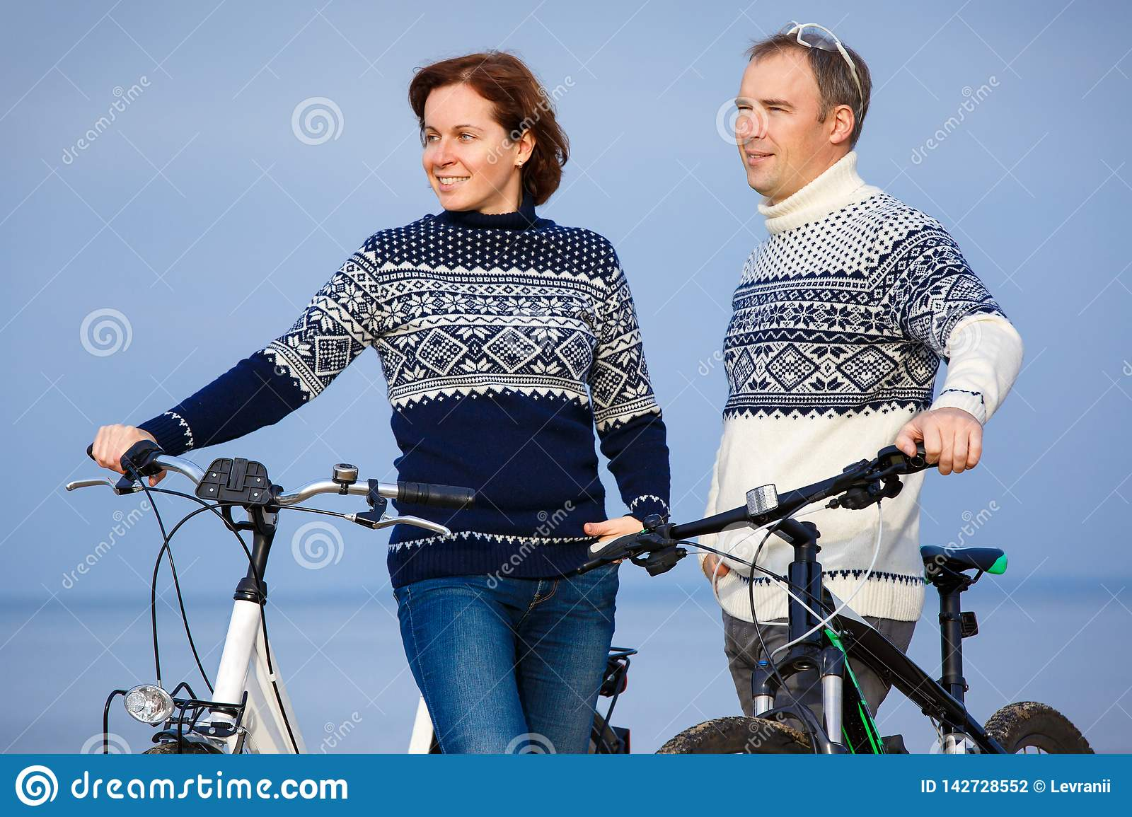 Cheerful young couple biking on beach outdoors. Cheerful young couple biking on beach on a sunny day stock photography