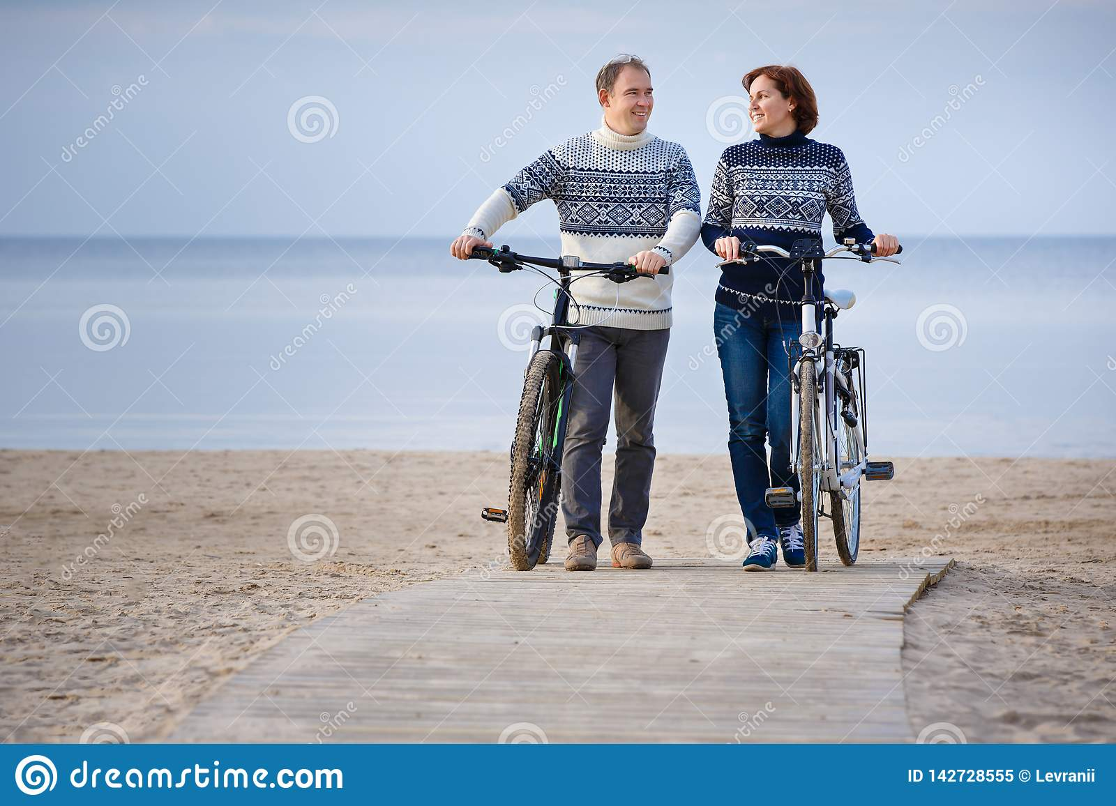 Cheerful young couple biking on beach outdoors. Cheerful young couple biking on beach on a sunny day royalty free stock photo