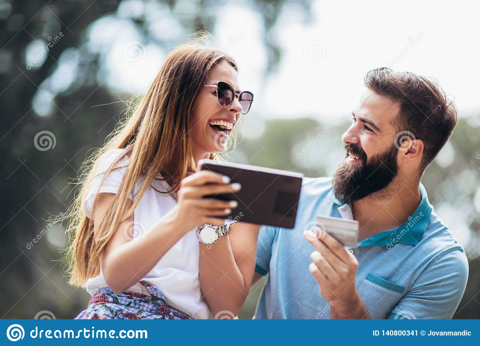 Young couple sitting on a park bench and uses a digital tablet for online shopping