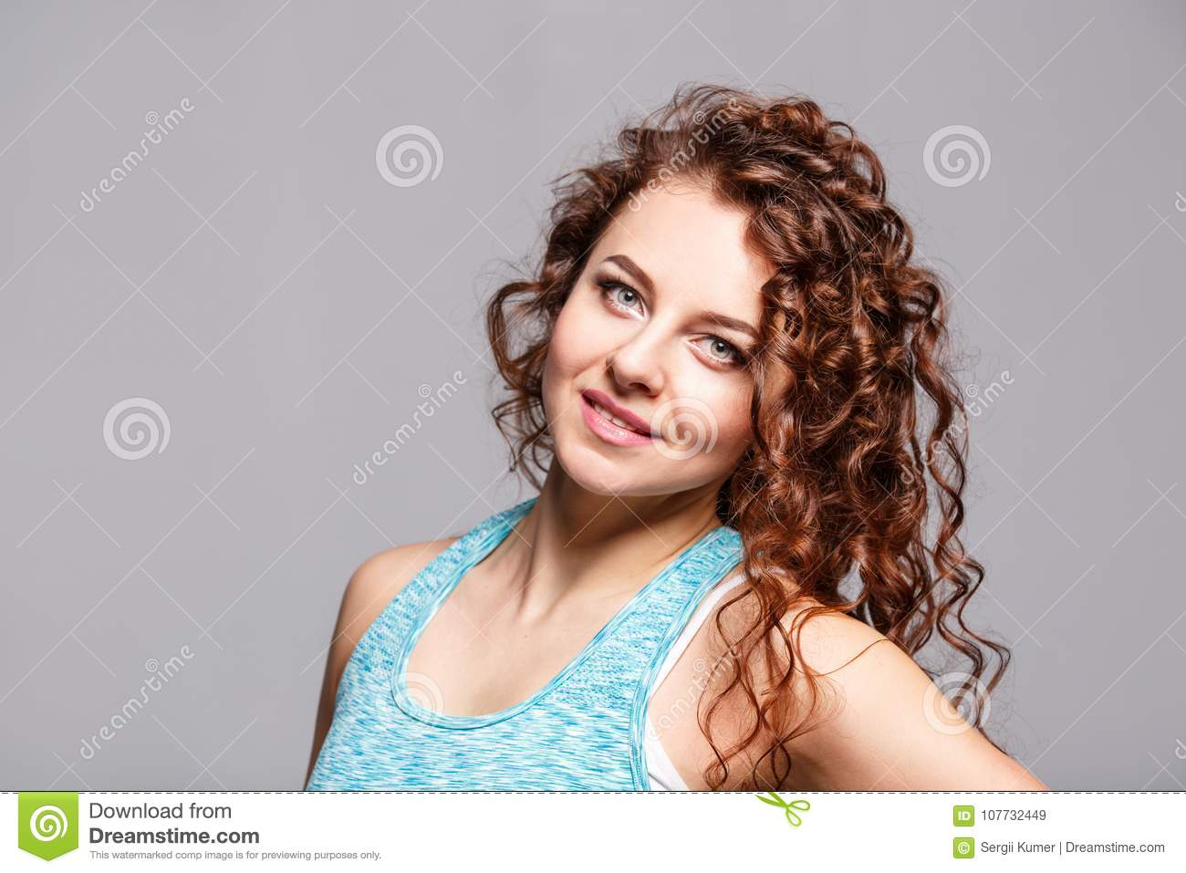 b97d5f27 Cheerful young fitness woman standing against grey background with copy  space